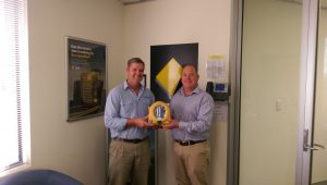 Steve Mitchell President NCFC receiving AED from Shane Dowton CBA supporter of Donate a Battery to Jump Start a Heart