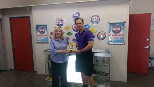 Jared Cox of Battery World presenting AED to Kylie O'Leary of PCYC Tamworth